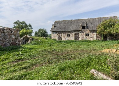 The farmyard is an agricultural abandoned farm. The old collapsed barns. The entrance to the cellar is like a cave. The end of the summer . Podlasie, Poland.