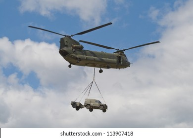 FARNBOROUGH - JULY 24: A British Army Boeing CH-47 carrying a Land Rover at Farnborough 2010 Airshow, July 24, 2010, Farnborough, England. Over 1,179 Chinook's have been built .