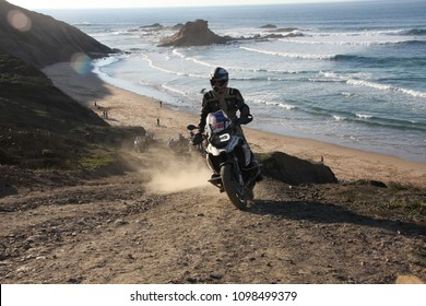 Faro, Portugal, 02.23.2018. A motorbiker riding enduro up to the hill from the beach.