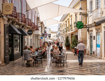 FARO, PORTUGAL - 6 AUGUST 2018: Diners enjoying the warm Portuguese weather as they dine al fresco in the pedestrianised shopping district of central Faro.