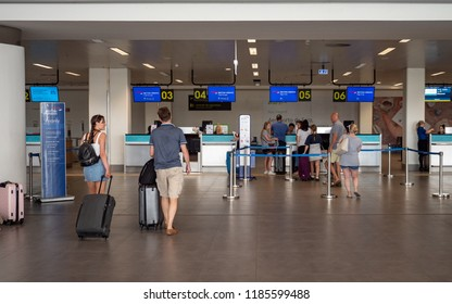 FARO, PORTUGAL - 6 AUGUST 2018: A smiling couple of tourists making their way to the check-in desk for the British Airways airline at Faro International Airport, Portugal.