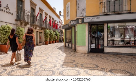 FARO, PORTUGAL - 6 AUGUST 2018: Female shoppers walking through the pedestrianised central shopping district of Faro. Note the familiar cobbled streets.