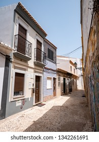 FARO, PORTUGAL - 6 AUGUST 2018: Closed and shuttered homes sheltering from the heat of the sun in the back streets of central Faro, Portugal.