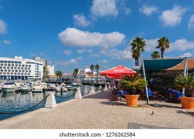 FARO, PORTUGAL - AUGUST 30, 2017: Tourists walk along the promenade past motor boats in marina