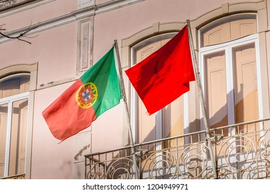 Faro, Portugal - May 1, 2018: Portuguese flag and communist party flag on a building facade