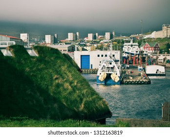 Tórshavn, Faroe Islands - May 28, 2018. Urban skyline with Torshavn Port and distant city over the Vestara Vág from Tinganes peninsula with historic grass-roofed house in foreground.