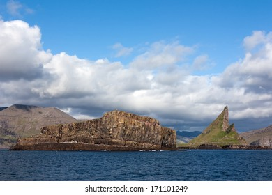 Faroe Islands, natural landscape caught from the sea . Rocky islets with steep cliffs overlooking the sea