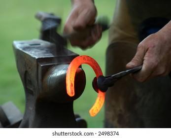 Farrier shaping hot shoe