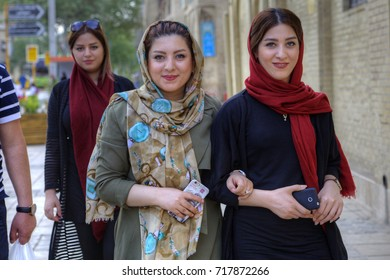 Fars Province, Shiraz, Iran - 18 april, 2017: Young Iranian women, dressed in hijab, are walking along a city street with smartphones in their hands.