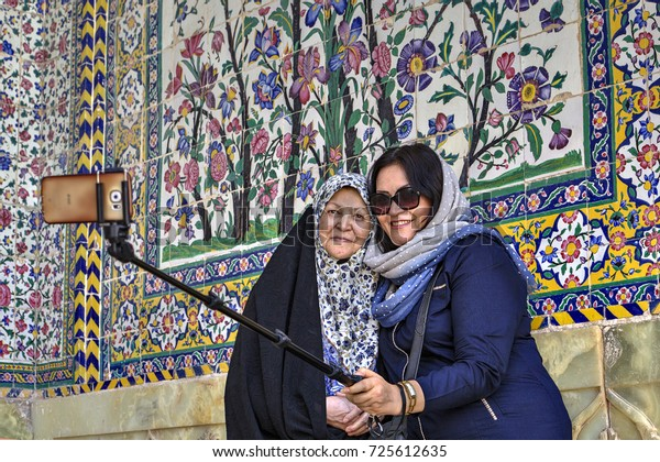 Fars Province, Shiraz, Iran - 19 april, 2017: Two Muslim women dressed in hijabs, photograph themselves using a selfie stick and smartphone, in the inner courtyard of the Regents mosque.