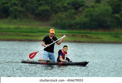 The Farther and son Playing Stand up paddle boards (SUP) offer a fun, relaxing way to play on the water, Cam Son Lake, Bac Giang, Viet Nam 2016