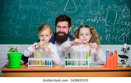Fascinating biology lesson. Man bearded teacher work with microscope and test tubes in biology classroom. School biology experiment. Explaining biology to children. How to interest children study.