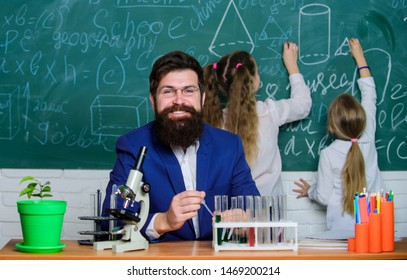Fascinating biology lesson. School teacher of biology. Man bearded teacher work with microscope and test tubes in biology classroom. Explaining biology to children. How to interest children study.