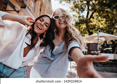 Fascinating blonde girl making selfie on the street with friend. Stunning young ladies enjoying spring day.