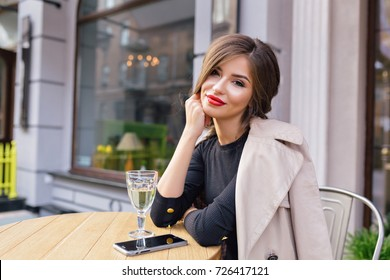 fascinating brunette with stylish collected hairstyle and red lipstick is sitting on summer terrace with a glass of wine and smiling at camera. Outdoor portrait of attractive woman in restaurant.
