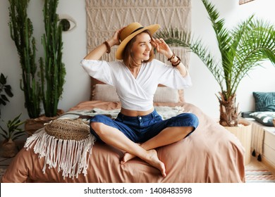 Fascinating brunette woman chilling at home in cozy boho interior. Macrame on wall. Palm trees and cactus on background.