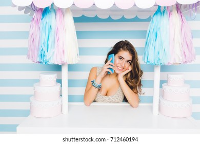 Fascinating cheerful girl wearing bracelet speaking on mobile phone standing behind counter with cakes. Adorable young woman with beautiful smile calling her friend during selling desserts.