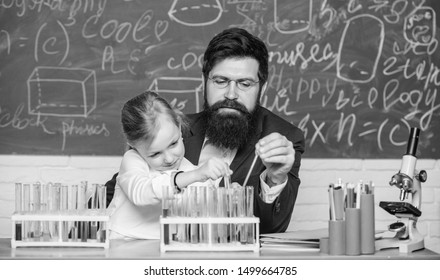Fascinating chemistry lesson. Man bearded teacher and pupil with test tubes in classroom. Private lesson. School chemistry experiment. Explaining chemistry to kid. How to interest children study.