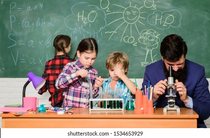Fascinating chemistry lesson. Man bearded teacher and pupils with test tubes in classroom. Observe reaction. Science is always the solution. School chemistry experiment. Explaining chemistry to kids.