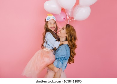 Fascinating curly mother and beautiful little daughter in the same attire posing together after birthday party. Portrait of charming girl in lush skirt hugs her elder sister with love and smile