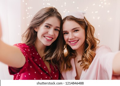 Fascinating dark-haired girl wears red night-suit making selfie with smiling sister. Indoor photo of two lovely ladies in cute pyjamas taking picture of themselves.