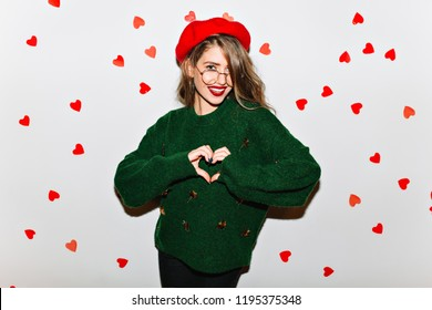 Fascinating glamorous girl expressing love on white background. Carefree female model in french outfit celebrating valentine's day.