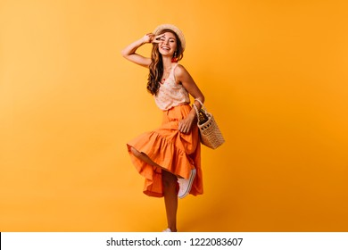 Fascinating red-haired lady expressing positive emotions. Happy ginger girl in orange skirt dancing with smile.