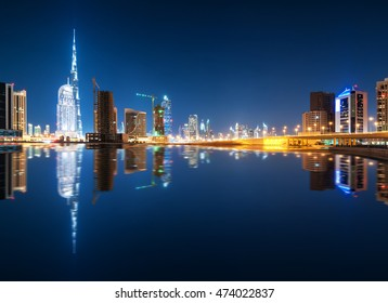Fascinating reflection of tallest skyscrapers in Business Bay district during calm night. Downtown summer night. Construction built at night time. Dubai, United Arab Emirates.