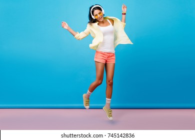 Fascinating slim girl with black hair jumping and singing, enjoying good summer day. Funny young woman with tanned skin wears sneakers and cotton clothes dancing on blue background.
