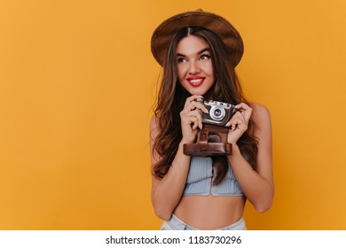 Fascinating young female photographer having fun after photoshoot. Romantic brunette girl in hat standing in studio with camera.