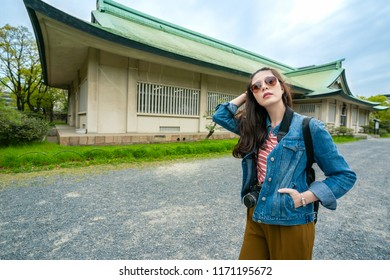 fashinable travle woman posing and putting hand in pocket while sightseeing in osaka castle with sunny blue sky.
