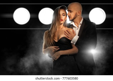 fashioable young couple in love posing and hugging in suit and dress in studio on dark background with smoke