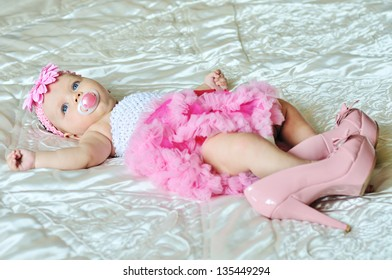 fashion 3 months old baby girl laying on the bed with high heels shoes
