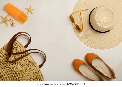 Fashion accessories for the beach - hat, ballet shoes, orange glasses and sunscreen on a white background. Selective focus.