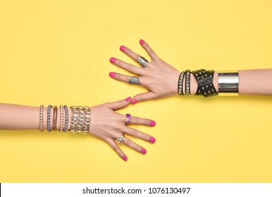 Fashion Accessories Set. Female hand, Stylish Trendy Jewelry, Glamor bracelets Ring. Minimal Design. Summer Girl Outfit. Hipster Essentials. Creative Art. Friendship concept on Yellow