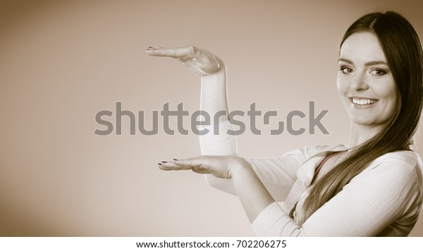 Fashion and advertisement concept. Smiling woman holding open palm empty hand showing copy space holding your product.