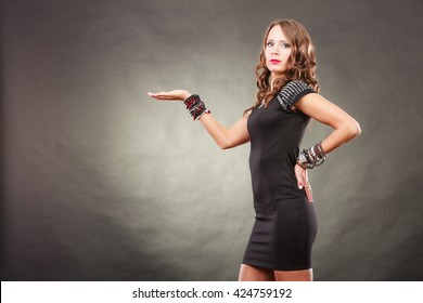 Fashion and advertising concept. Pretty young woman wearing bracelets jewellery in black elegant evening dress showing empty hand open palm with copy space