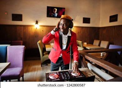 Fashion african american man model DJ at red suit with dj controller.