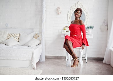 Fashion african american model in red beauty dress, sexy woman posing evening gown sitting at chair against mirror in white vintage room.
