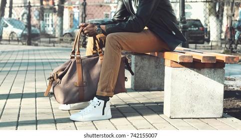 Modeman met tas zit op een bankje in de stad close-up