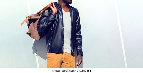 Fashion african man wearing a black biker leather jacket holds a bag over gray background