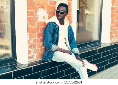Fashion african man wearing jeans jacket with hood poses on city street on brick wall background