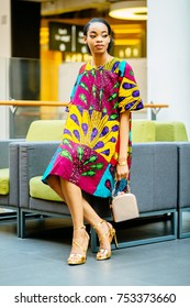 Fashion african woman in national dress sitting in armchair at shopping center. People and lifestyle concept.