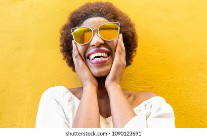 Fashion african woman smiling and wearing sunglasses with yellow ochre background - Black afro girl having fun - Focus on face - Youth lifestyle, trendy and happiness concept