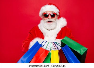 Fashion aged mature stylish client Saint Nicholas in tradition costume spectacles headwear gloves white beard with winter noel eve wish package stand glad isolated on red vivid background