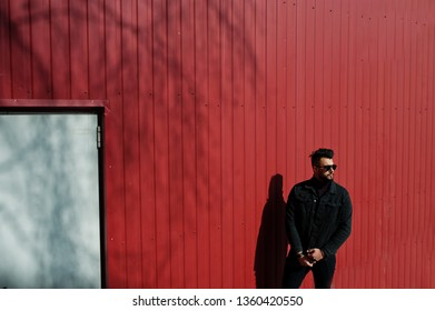 Fashion Arab man wear on black jeans jacket and sunglasses posed against red steel wall background. Stylish and fashionable arabian model guy.