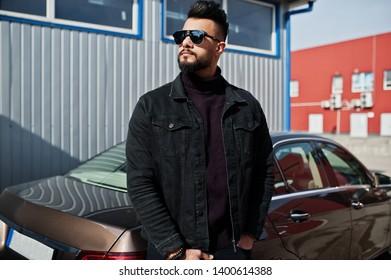 Fashion Arab man wear on black jeans jacket and sunglasses posed against business modern car. Stylish, succesful and fashionable arabian model guy.
