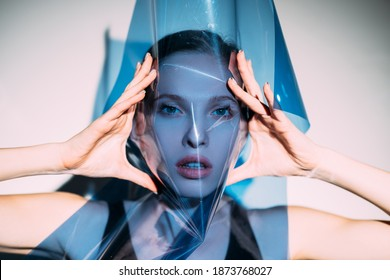 Fashion art. Beauty portrait. Professional photoshoot. Vogue trend. Gorgeous model woman covering face with blue colored transparent filter in spotlight.