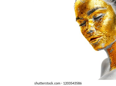 Fashion art Golden skin Woman face portrait closeup. Model girl with cracked gold foil on skin. Glamour shiny professional makeup. Jewellery, accessories. Beauty gold metallic body, Lips and Skin.