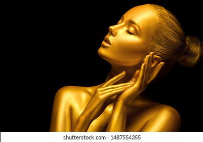 Fashion art Golden skin Woman face portrait closeup. Model girl with holiday golden Glamour shiny professional makeup. Gold jewellery, jewelry, accessories. Beauty gold metallic body, painted Skin